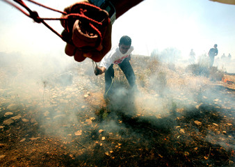A Palestinian youth tries to extinguish a fire after Israeli troops fired tear gas canisters during ...