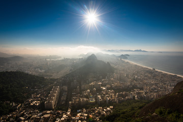 Fototapete - Aerial View of Copacabana District, the Sugarloaf Mountain in the Horizon, Sun Shines Above, Rio de Janeiro, Brazil