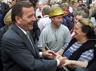 German Chancellor Gerhard Schroeder shakes hands with an unidentified woman during his visit to Nord..