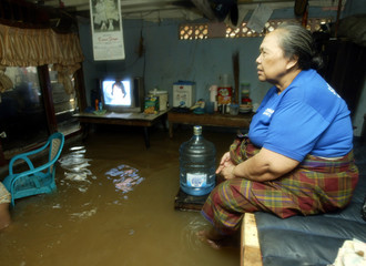 AN INDONESIAN WOMAN SITS IN HER FLOODED ROOM IN JAKARTA.