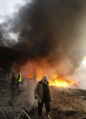 Palestinians inspect a burning building following an Israel air strike in Gaza Strip