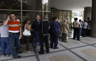 People line up outside a branch of Stanford International in Caracas
