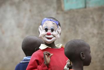 A boy wearing a cartoon mask gestures to the photographer in Nairobi's Kibera slum