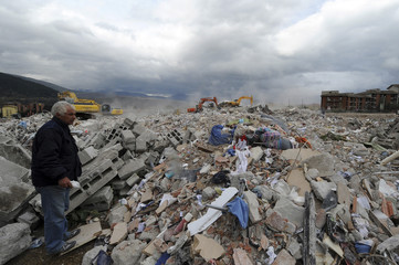 Man looks for his belongings as excavators dig through rubble of buildings after earthquake in L'Aquila