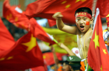 A young Chinese supporter cheers during a semi-final match between China and Iran at the Asian Cup in ...