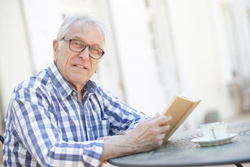 Elderly man with eyeglasses reading book outside