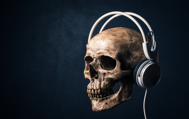 human skull listening with headphones on art dark background