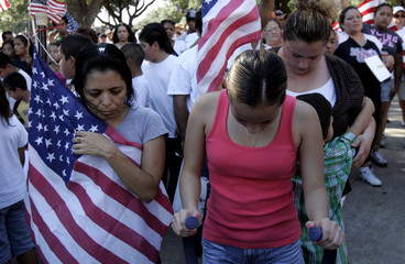 Pro immigration rights supporters bow their heads in prayer during a rally in Irving