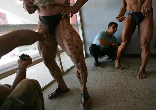 Men apply tanning lotion onto body builders as they prepare for a competition for the title of Mr Afghanistan in Kabul