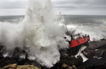 A wave crashes against the hull of the merchant ship Maro, wrecked near the Basque port town of Hondaribbia