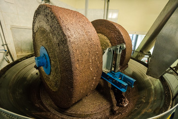 Extraction of oil from olives using a circular grinding stone.