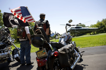 Members of motorcycle veterans group Rolling Thunder watch as Marine One lands with U.S. President George W. Bush onboard at the South Lawn of the White House