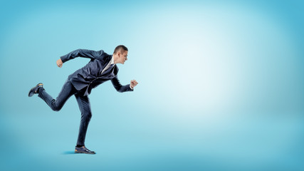 A businessman in a runner position ready to start on blue background. New business.