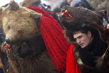 Men dressed in bear costumes take part at the Lole Carnival