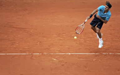 Switzerland's Federer serves to Russell of the U.S. during the French Open tennis tournament at Roland Garros in Paris