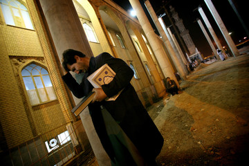 Iranian man attends prayer ceremony to commemorate anniversary of death of Imam al-Ali south of Tehran
