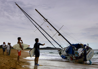 Surfers look at a yacht that was washed up onto shore on Sydney's Narrabeen Beach