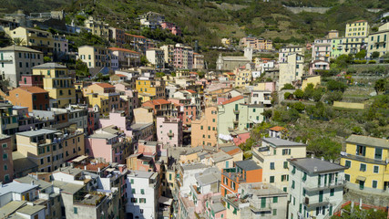 Aerial video footage with drone on Riomaggiore, one of the famous Cinqueterre country, small village with colored houses on the cliff over the sea
