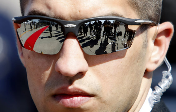 Media corps and honour guards are reflected on sunglasses wore by a Israeli security agent in Tokyo