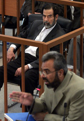Former Iraqi president Hussein looks at witness Al Dujaili testify during Hussein's trial in Baghdad