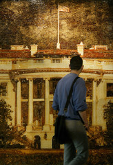 A man looks at a picture of the White House made of smoked cold cuts and cheese on wood at an art ...