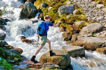 Female hiker crossing a mountain stream on stepping stones