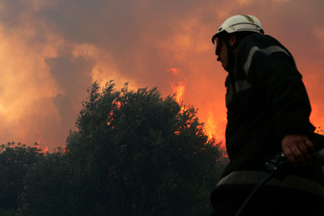 French firefighter walks with walkie-talkie as flames from wildfire burns forest in Boulternere, in ...