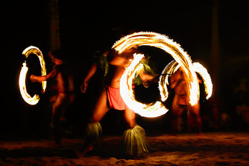 Fire dancers at Hawaii luau show, polynesian hula dance men jugging with fire torches.