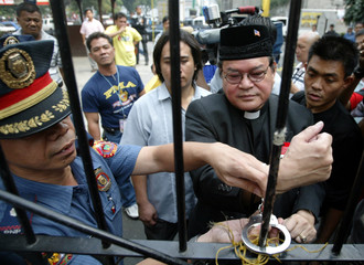 POLICEMAN REMOVES HANDCUFF OF DISQUALIFIED PRESIDENTIAL CANDIDATE IN MANILA.