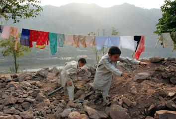 Kashmiri boys work to remove debris in a village north of Muzaffarabad