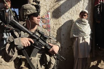 U.S Army soldier from Task Force Denali 1-40 CAV combat team keeps watch while his comrade collect information on shops owners at the bazaar during a patrol in town of Saway-kowt in Khowst province