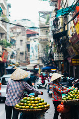 Hanoi, Vietnam - December 31, 2016: The street vendors in Hanoi, Vietnam. Woman selling fruits in the early morning on a busy street.