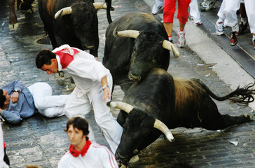 A runner tries to get away from the bulls during San Fermin's third running of the bulls in Pamplona.
