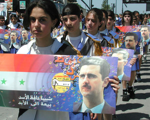 Young Syrian women carry the portrait of designated Syrian leader Bashar al-Assad through the street..