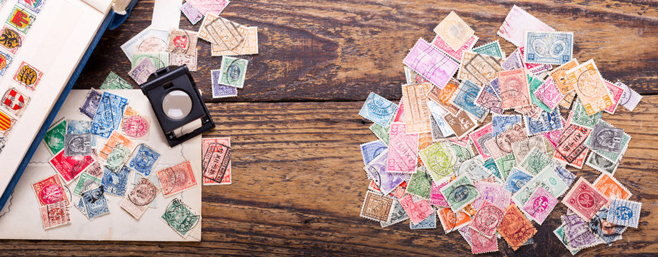 Old postage stamps and magnifying glass