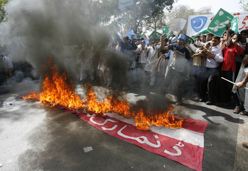 Supporters of Islami Jamiat-e-Talba group burn a mock Danish flag during a rally in Lahore
