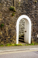 open wooden door with pointed gothic arch on a white stone wall ,  wall consists of irregluar stone blocks, old architecture