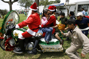 Traffic police officers dressed up as Santa Claus ride on their motorcycles with children during their visit to a hospital to distribute gifts during the Christmas season in Lima