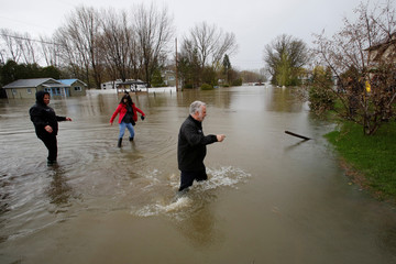 Quebec Premier Couillard walks through water while touring a flooded residential area in Rigaud