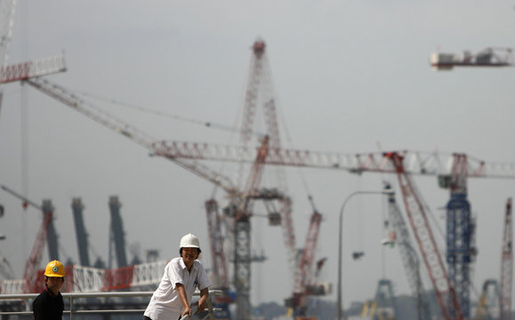 Construction workers stand on a ledge at a site near Singapore's financial district with cranes at the Marina Bay Sands casino site in the background