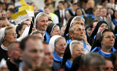 A nun holds small Vatican flags during a mass of Pope Benedict XVI in the basilica of Altoetting