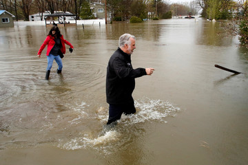 Quebec Premier Couillard walks through the water while touring a flooded residential area in Rigaud