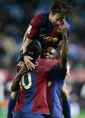 Barcelona's Eto'o celebrates goal with Ronaldinho and Puyol after scoring against Atletico Madrid during their soccer match in Madrid