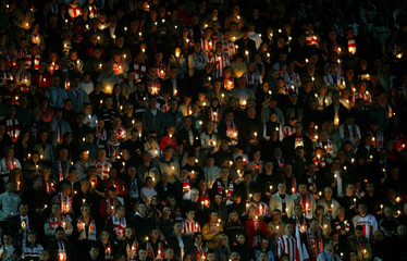 Polish soccer fans cry during a mass to honour the late Pope John Paul II at the Cracovia stadium in ...