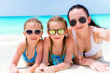 Mother and little girls taking selfie at beach lying on white sand. Happy family take selportrait relaxing on vacation