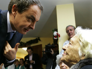 Spanish Prime Minister Zapatero speaks with an old woman during a visit to an old people's home in Seville.