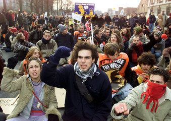 Anti-globalisation activists raise their fists while sitting in the street during a demonstration in..