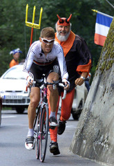 Deutsche Telekom rider Jan Ullrich (C) of Germany is encouraged by a fan dressed in a devil's costum..