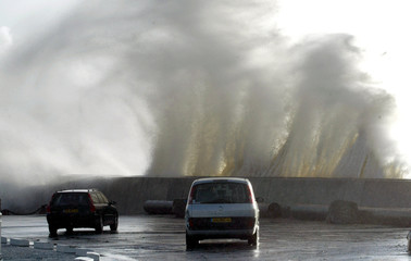 Big waves hit Pornic port walls as cars are parked nearby during a strong storm blowing in French Britany region, western France