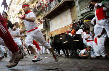Bull runner is knocked down by bull during first running of bulls in Pamplona